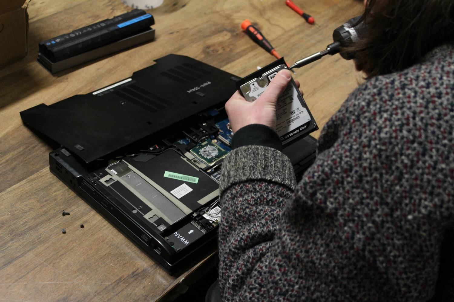 A laptop computer being opened for repair.