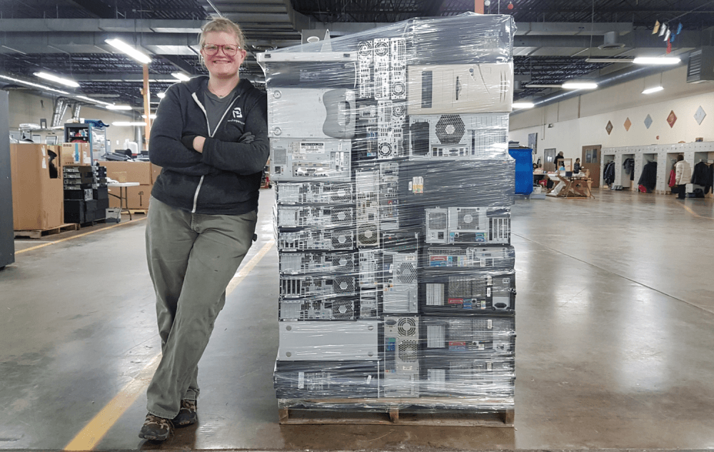 Warehouse and Production Supervisor Abbey Dibble Poses Next to a Pallet of E-Waste